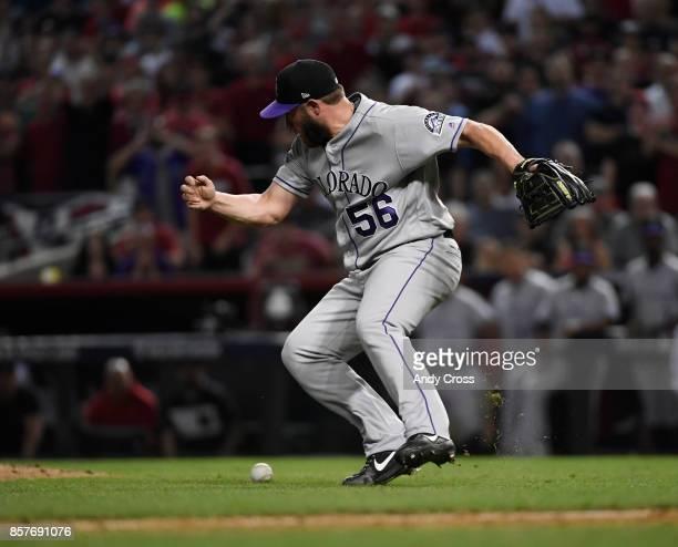 Colorado Rockies pitcher Greg Holland #56 was unable to pick up a dribbler hit by Arizona Diamondbacks catcher Jeff Mathis scoring Arizona...