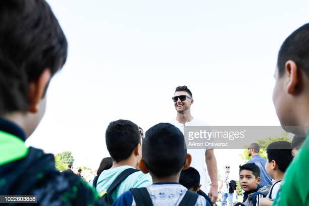 Colorado Rockies pitcher Kyle Freehand hands out backpacks to students on the playground at Holm Elementary during a surprise visit on Friday August...