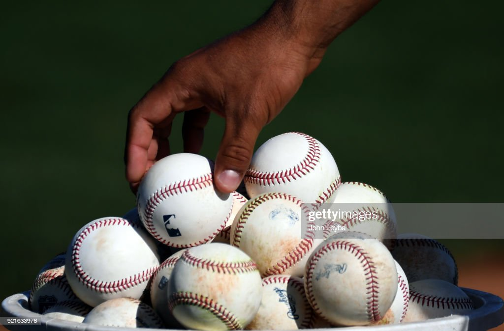 Colorado Rockies players carefully places a baseball in the bucket to knock down the others during drills on February 20, 2018 at Salt River Fields at Talking Stick in Scottsdale, Arizona.