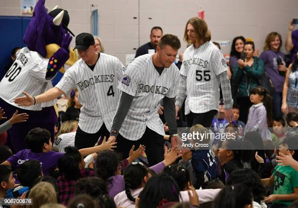 Colorado Rockies players Pat Valaika left Kyle Freeland center and Jon Gray right greet Holm Elementary School students during their entrance for the...