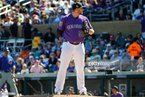 Colorado Rockies relief pitcher Brooks Pounders prepares to throw a pitch during the spring training baseball game between the Chicago Cubs and the...