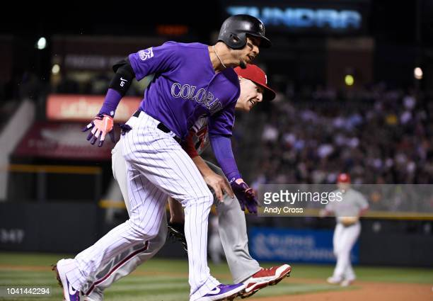 Colorado Rockies right fielder Carlos Gonzalez beats out a throw to Philadelphia Phillies first baseman Rhys Hoskins in the 4th inning scoring...