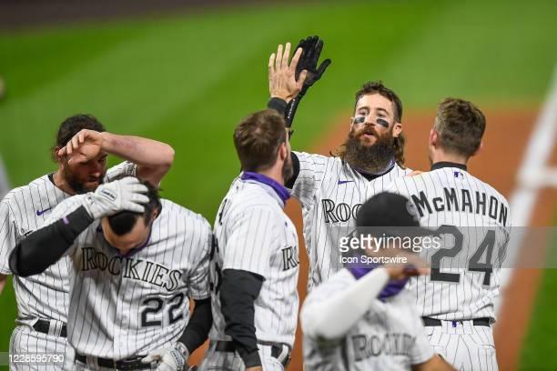Colorado Rockies right fielder Charlie Blackmon is congratulated by third baseman left fielder David Dahl after hitting a ninth inning walk-off grand...