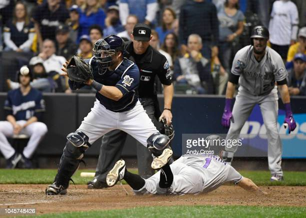 Colorado Rockies second baseman Garrett Hampson slides across home plate against Milwaukee Brewers catcher Manny Pina in the 9th inning from a sac...