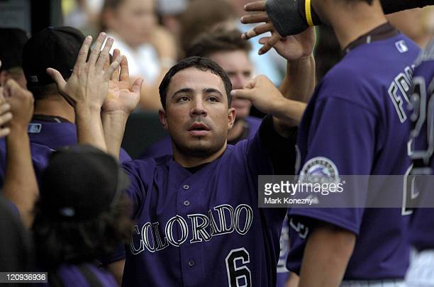 Colorado Rockies second baseman Omar Quintanilla is congratulated by teammates in the dugout after scoring a run during a game against against the...