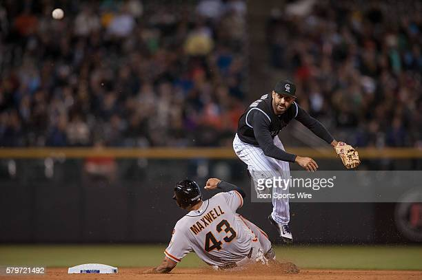 Colorado Rockies shortstop Daniel Descalso leaps over a sliding San Francisco Giants right fielder Justin Maxwell for a double play during a regular...