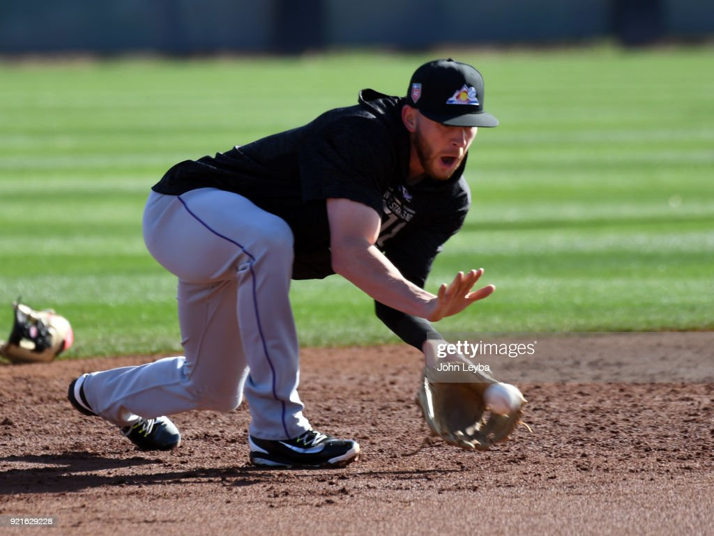 Colorado Rockies shortstop Trevor Story (27) scoops a grounder during the teams workout on February 20, 2018 at Salt River Fields at Talking Stick in Scottsdale, Arizona.