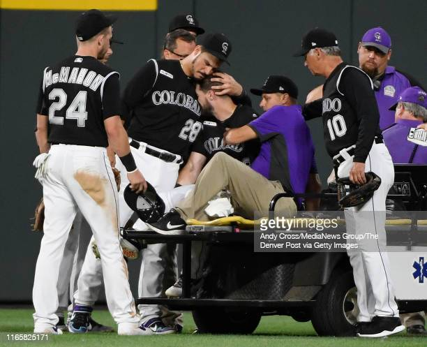 Colorado Rockies third baseman Nolan Arenado consoles center fielder David Dahl as Dahl gets transported off the field with a right leg injury going...