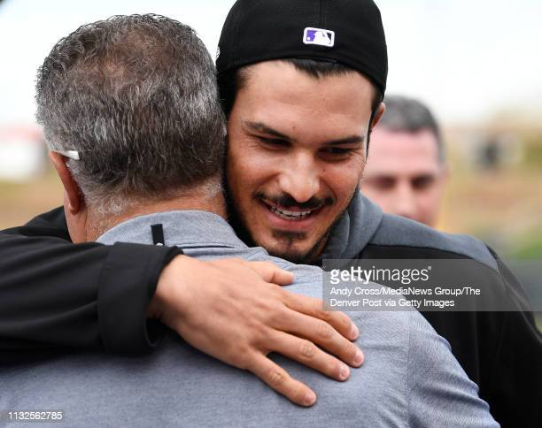 Colorado Rockies third baseman Nolan Arenado hugs his father Fernando before taking the riser for his press conference at Salt River Fields February...
