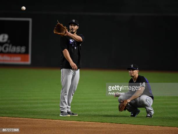 Colorado Rockies third baseman Nolan Arenado left and Colorado Rockies catcher Tony Wolters retrieving baseballs during practice at Chase Field...