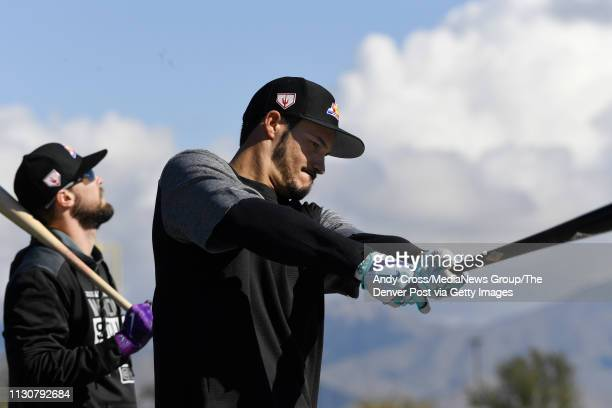 Colorado Rockies third baseman Nolan Arenado , right, follows through on his swing before entering the cage for batting practice at Salt River Fields...