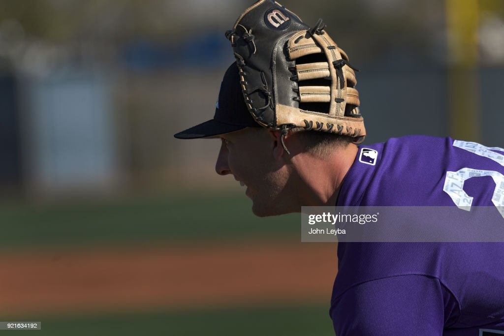 Colorado Rockies third baseman Ryan McMahon (24) picks up baseball as he wears his glove on his head after drills on February 20, 2018 at Salt River Fields at Talking Stick in Scottsdale, Arizona.