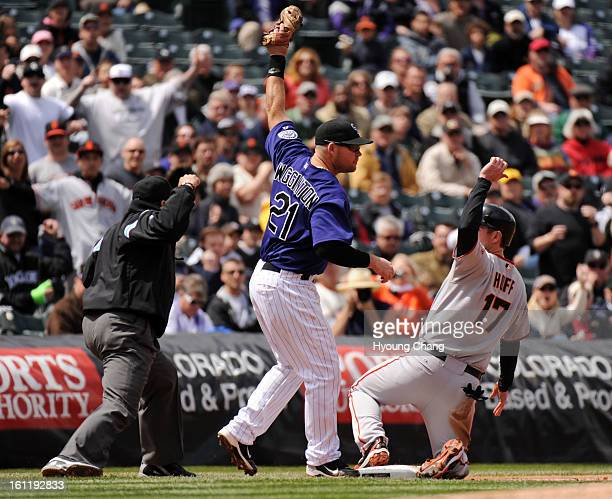 Colorado Rockies Ty Wigginton center tags San Francisco Giants Aubrey Hugg on the 3rd base in the 1st inning of the game at Coors Field on Wednesday...