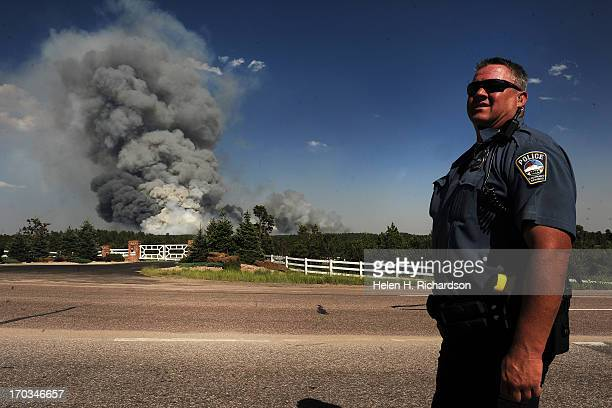 Colorado Springs patrolman Herb Tomitsch watches as a huge plume of smoke continues to grow along Highway 83 near Colorado Springs CO on June 11 2013...