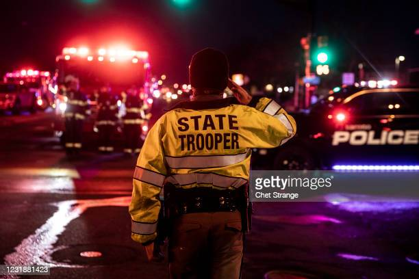 Colorado State Police officer salutes as a procession carrying the body of a fellow officer leaves King Sooper's grocery store where a gunman opened...