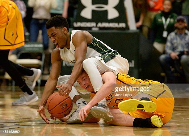 Colorado State Rams guard John Gillon scrambles on the floor for a loos ball with Wyoming Cowboys guard Jason McManamen with 53 second left in the...