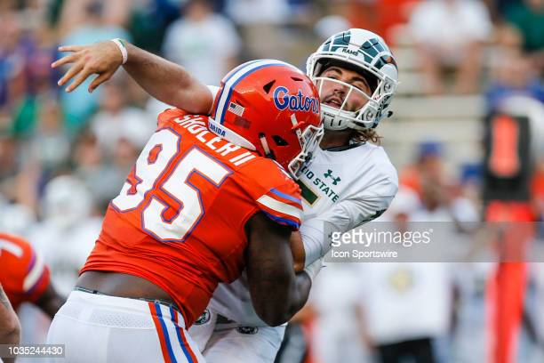 Colorado State Rams quarterback Collin Hill is hit by Florida Gators defensive lineman Adam Shuler during the game between the Colorado State Rams...