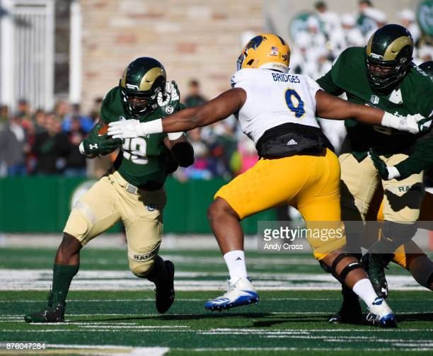 Colorado State Rams running back Rashaad Boddie brushes off San Jose State Spartans defensive tackle Bryson Bridges for a long gain in the first...