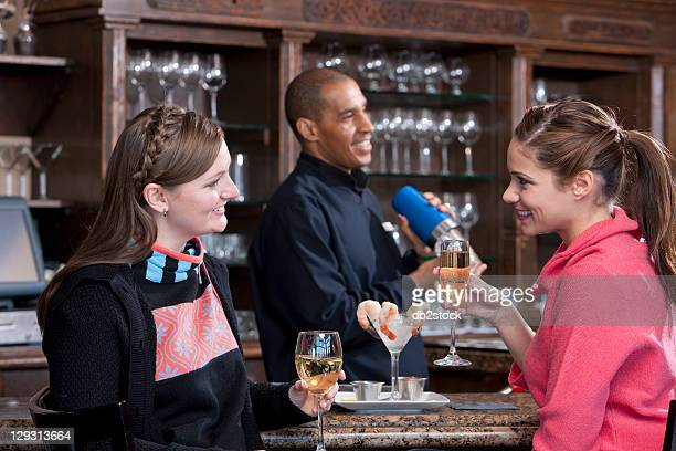 USA, Colorado, Telluride, Young women enjoying apres ski drink in bar