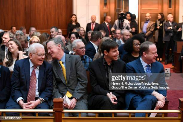 Colorado's new governor Jared Polis right sits with his partner Marlon Reis and former governors John Hickenlooper and Roy Romer left during the...