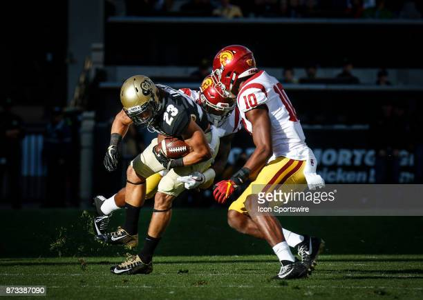 Colorado's Phillip Lindsay tries to escape a pair of USC defenders during the Colorado Buffalos game versus the USC Trojans on November 11 at Folsom...