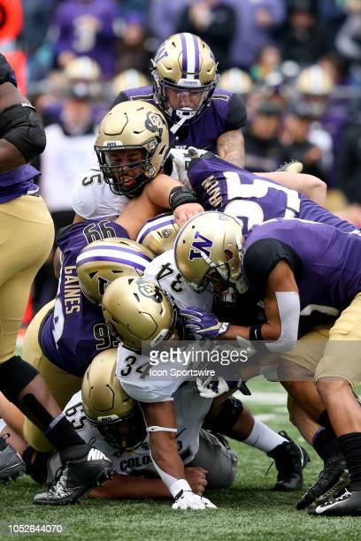 Colorado's Travon McMillian gets wrapped up at the line of scrimmage by Washington's Greg Gaines Ben BurrKirven and Myles Bryant during the college...