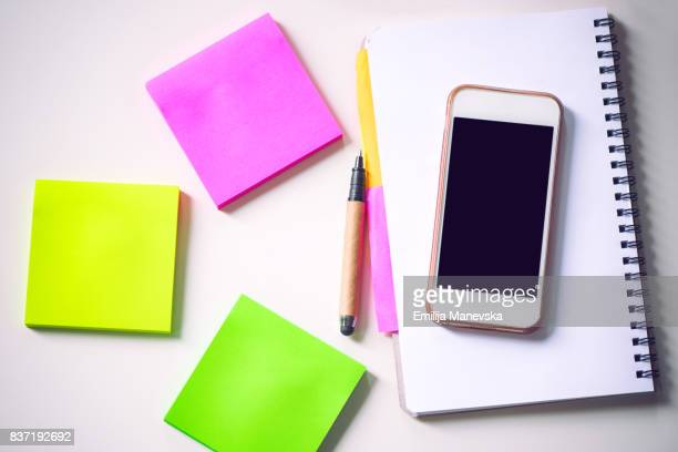 colored adhesive note and mobile phone on white desk. office supply - schulheft stock-fotos und bilder