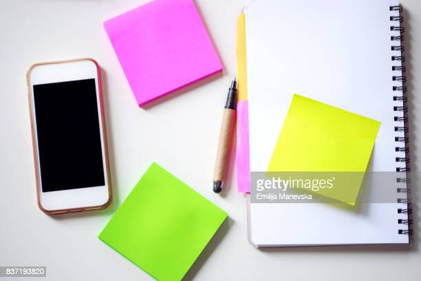 Colored adhesive note and mobile phone on white desk. Office Supply