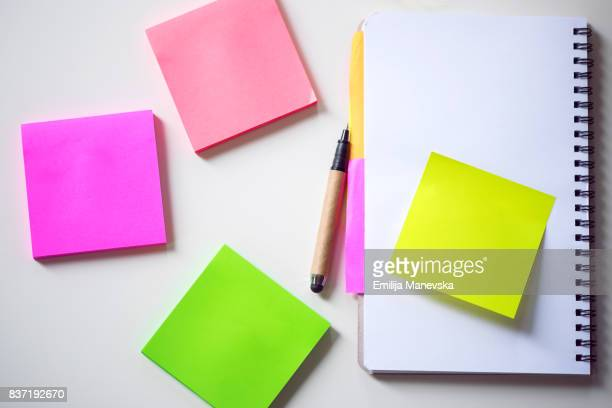 Colored adhesive note on white desk. Office Supply