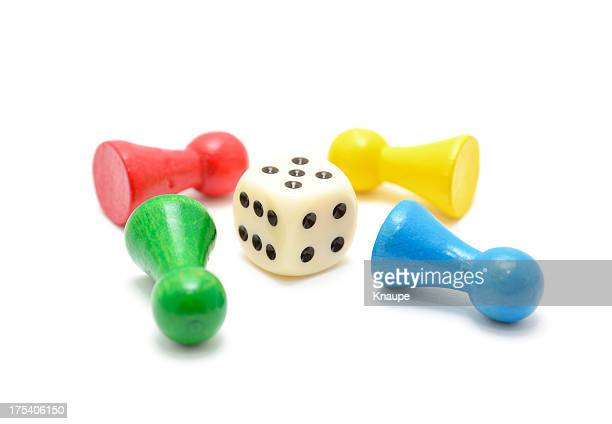 Colored  Board Game Pieces lie around dice on white background