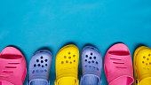 Colored bright slippers for women and children flip flops on a blue background. Place for text