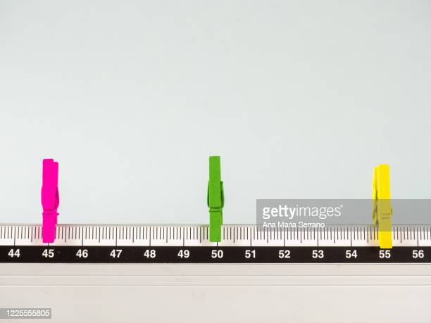 colored clothespins on a tape measure representing the concept of social distance - new normal stock pictures, royalty-free photos & images