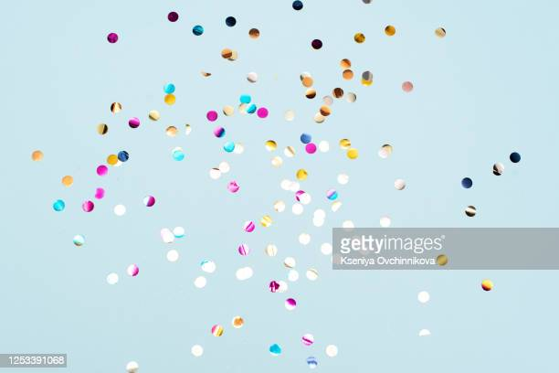 colored confetti flying in the blue sky. are small pieces or streamers of paper, mylar, or metallic material which are thrown at parades and celebrations. - jahrestag stock-fotos und bilder