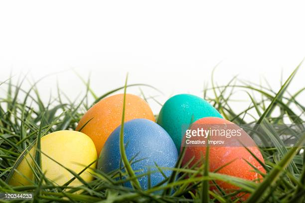 colored easter eggs in grass - easter religious background stock pictures, royalty-free photos & images