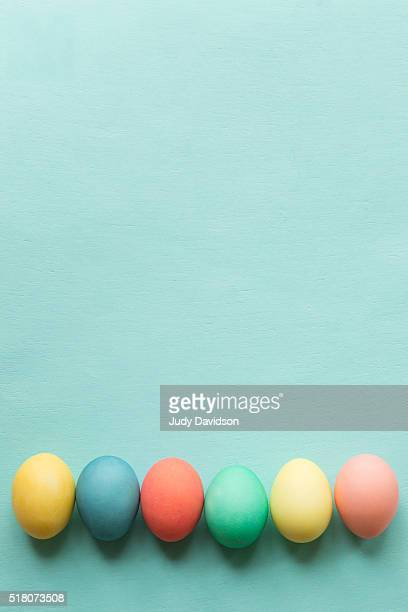 Colored Easter eggs lined up across the bottom of a plain aqua blue background with space for copy