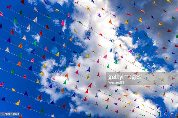 Colored flags against a blue sky