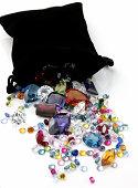 Colored Gemstones Spilling out of Black Bag