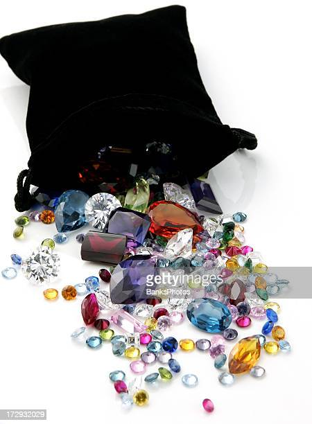 colored gemstones spilling out of black bag - diamond gemstone stock pictures, royalty-free photos & images