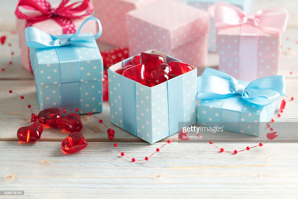 Colored gift boxes and red hearts on wooden planks : Stock Photo