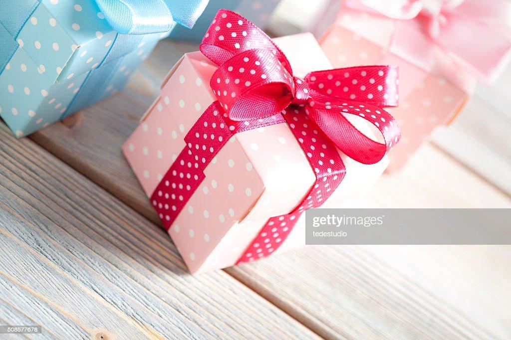 Bunte Geschenk-Boxen auf hölzernen Planken : Stock-Foto