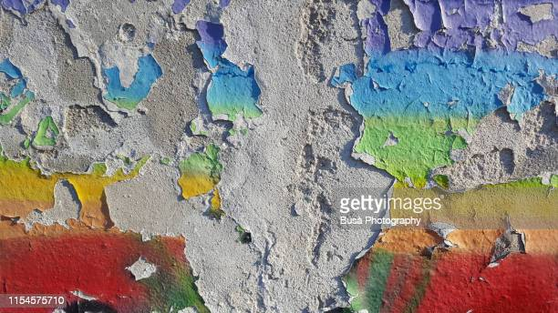 colored paint peeling off a street wall - prejudice stock pictures, royalty-free photos & images