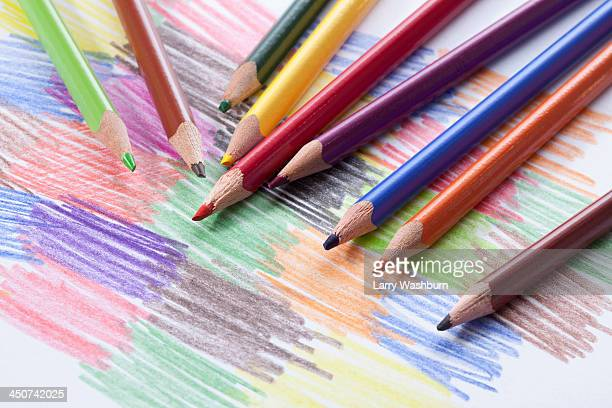 Colored pencils lying on a drawing with colored scribbles