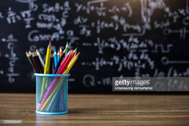 colored pencils on the blackboard background - riapertura delle scuole foto e immagini stock