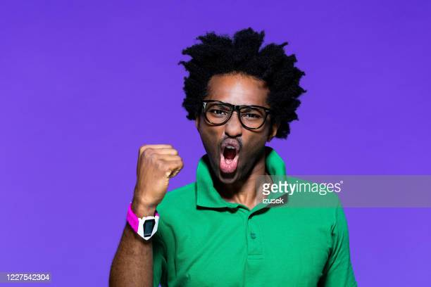 colored portrait of angry young man raising fist - striker stock pictures, royalty-free photos & images