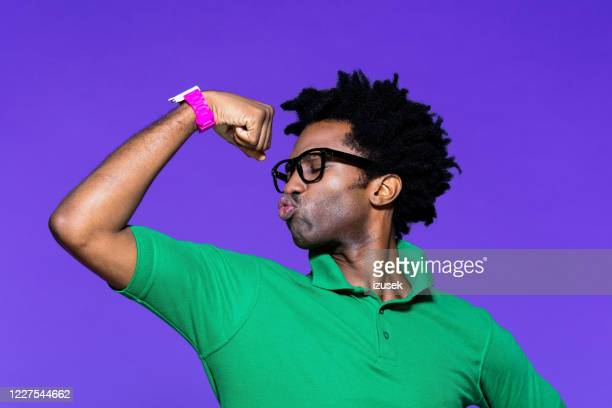colored portrait of funky young man with showing bicep - stiff stock pictures, royalty-free photos & images