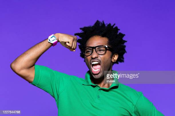 colored portrait of funky young man with showing bicep - success stock pictures, royalty-free photos & images