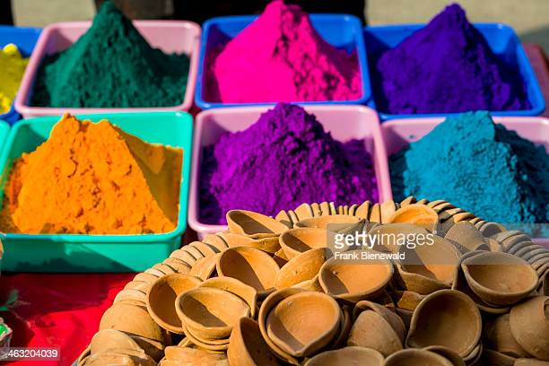 Colored powder in different colors is displayed in heaps for sale