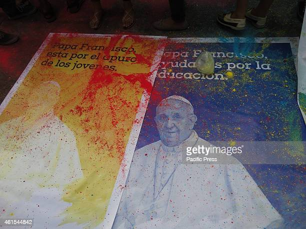 Colored powder lies on top of tarpaulins containing the image of Pope Francis along with messages in Spanish in front of the University of Santo...
