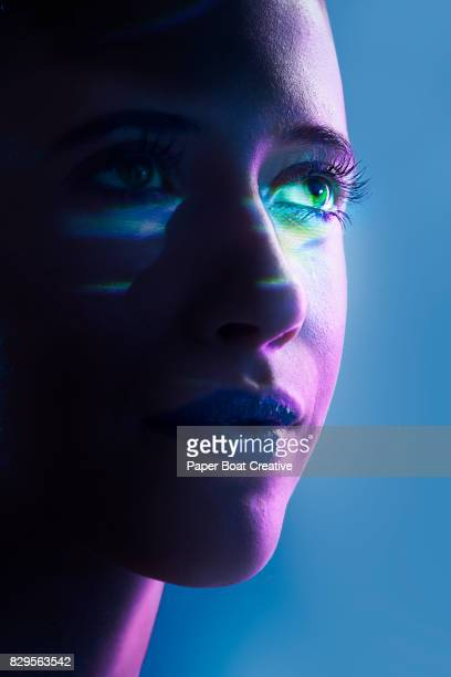 Colored prism with laser light reflecting on the face of a woman, shot close up against a blue background