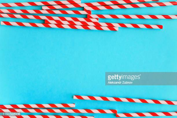 colored, red, reusable, paper, striped straws for drinking juice or cocktail life on blue background. - red tube stock photos and pictures
